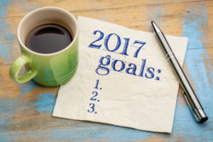 2017 goals list on a stained napkin against grunge wood table with a cup of coffee